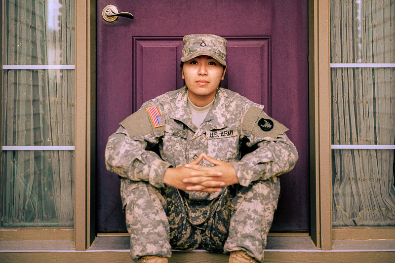 service member sitting in front of a door