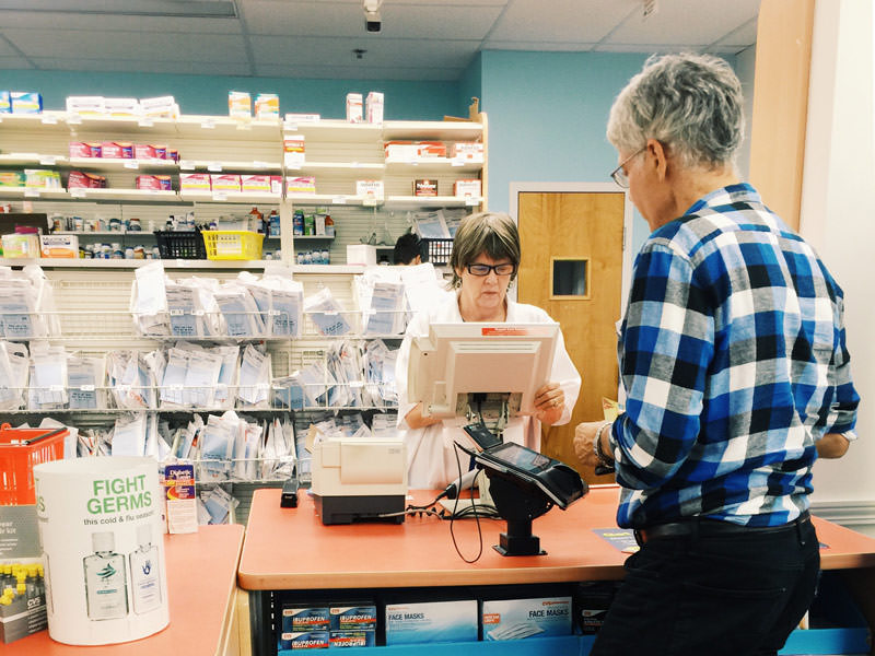 woman paying for medicine at pharmacy